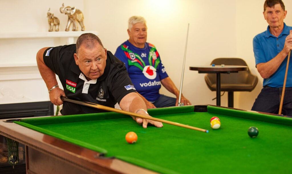 Older men playing pool in Independent Living Village