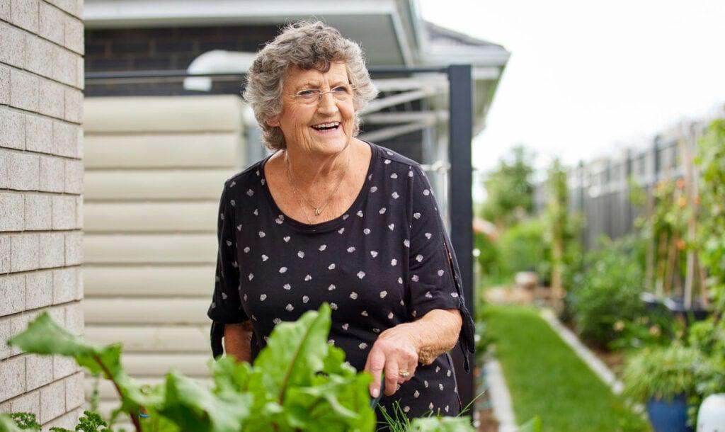 Smiling elderly woman tending to her garden at Retirement Village in Rotorua