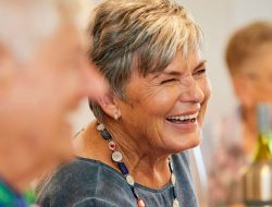 Laughing older woman enjoying a social event at an Independent Living facility