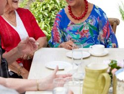 Laughing elderly woman sharing lunch inside Auckland Retirement Community