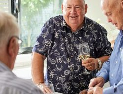 Older man talking to friends and drinking wine in kitchen at Rotorua Retirement Community